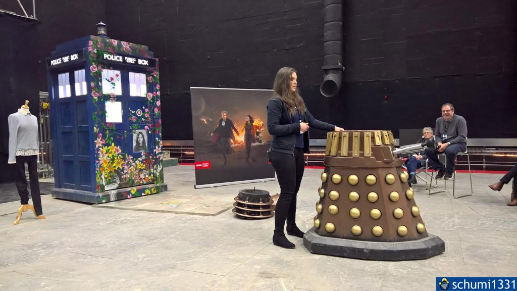 Mitarbeiterin erklärt, wie mit einem Dalek aufgenommen wurde. Links die Tribute-TARDIS für Clara